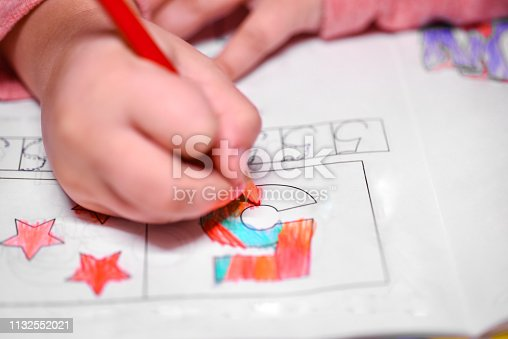 A girl learns to count, a girl colors a number five with a pencil