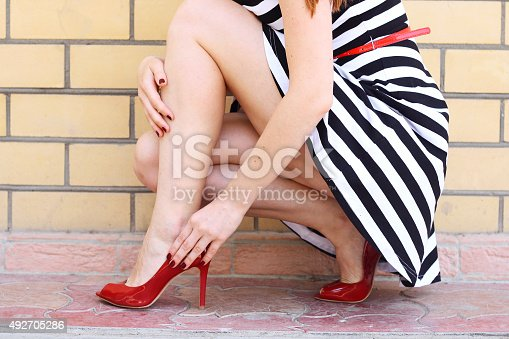 istock girl legs in red high heel shoes and  skirt outdoor 492705286