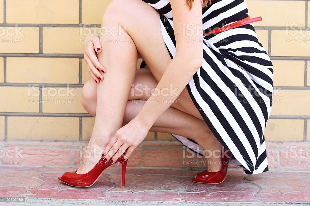 girl legs in red high heel shoes and  skirt outdoor stock photo