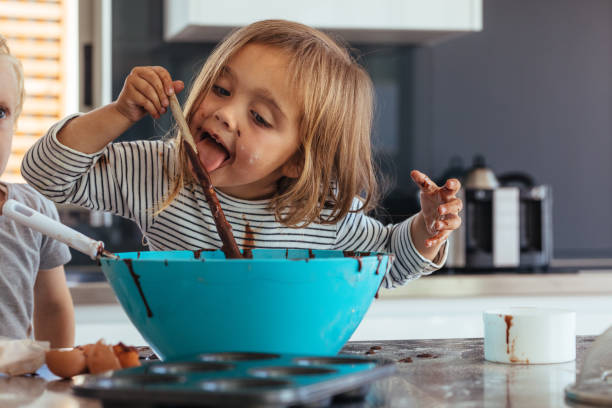 Girl licking chocolate cream while baking Little girl licking spoon while mixing batter for baking in kitchen  and her brother standing by. Cute little children making batter for baking. licking stock pictures, royalty-free photos & images