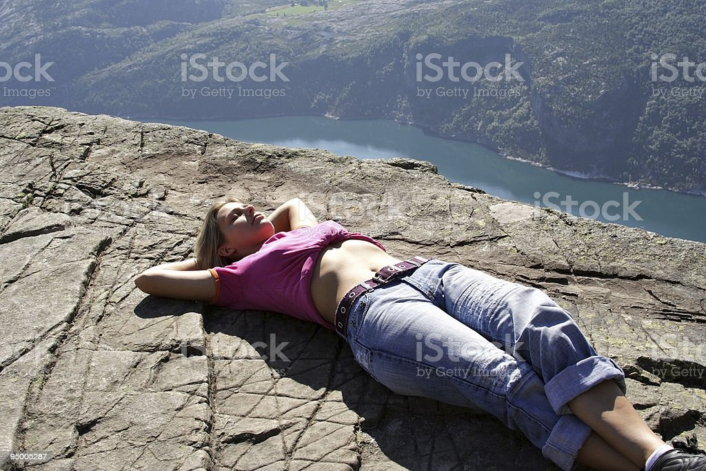 Girl lie on fjord cliff edge royalty-free stock photo