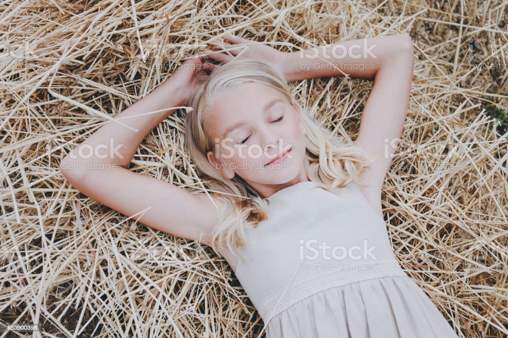 A girl lies on a hay. stock photo