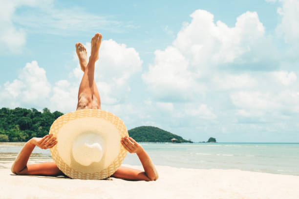 Girl lies on the white sand on the beach. Woman tanning relaxing on beach. Female adult from the back lying down with straw hat sunbathing under the tropical sun stock photo