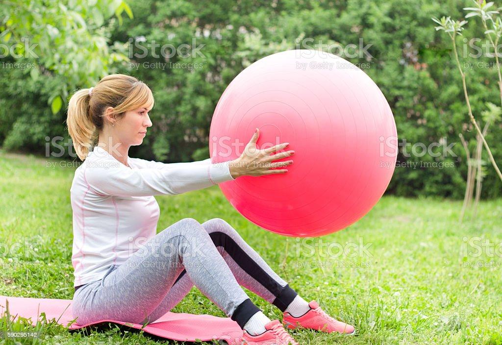 Girl lifting fitball in garden royaltyfri bildbanksbilder