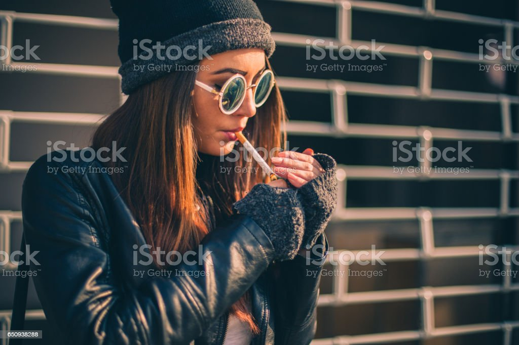 Girl lighting a cigarette stock photo