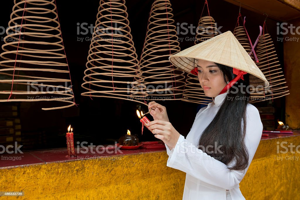Girl Lighting a Joss Stick at a Chinese Temple stock photo