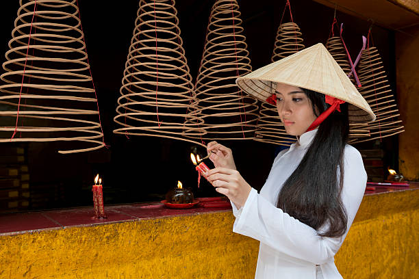 girl lighting a joss stick at a chinese temple - ao dai stock photos and pictures