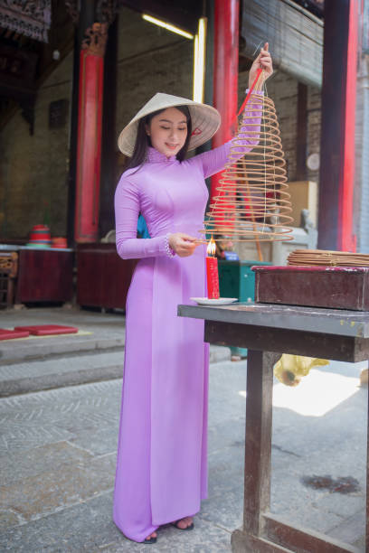 girl lighting incense stick at a chinese temple vietnam - ao dai stock photos and pictures