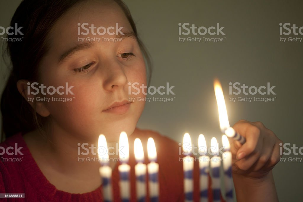 Girl lights menorah stock photo