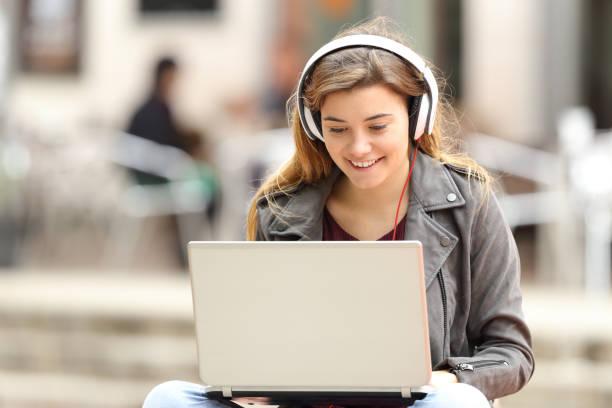女の子リスニング、ノート パソコンから音楽をダウンロード - ゲーム ヘッドフォン ストックフォトと画像