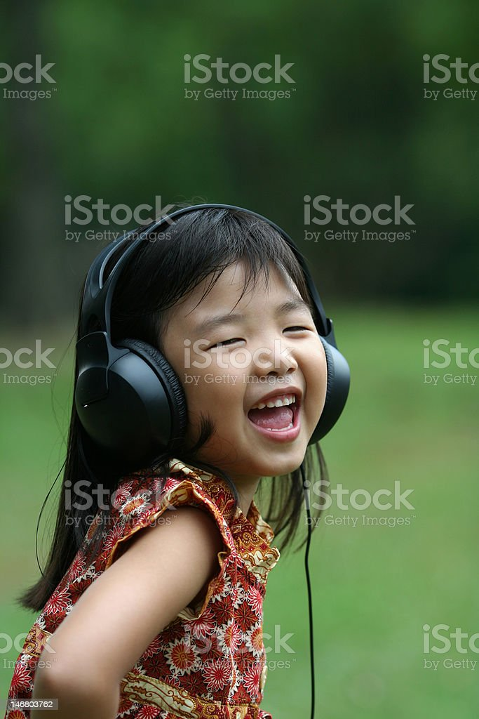 Girl listening and singing at the park royalty-free stock photo