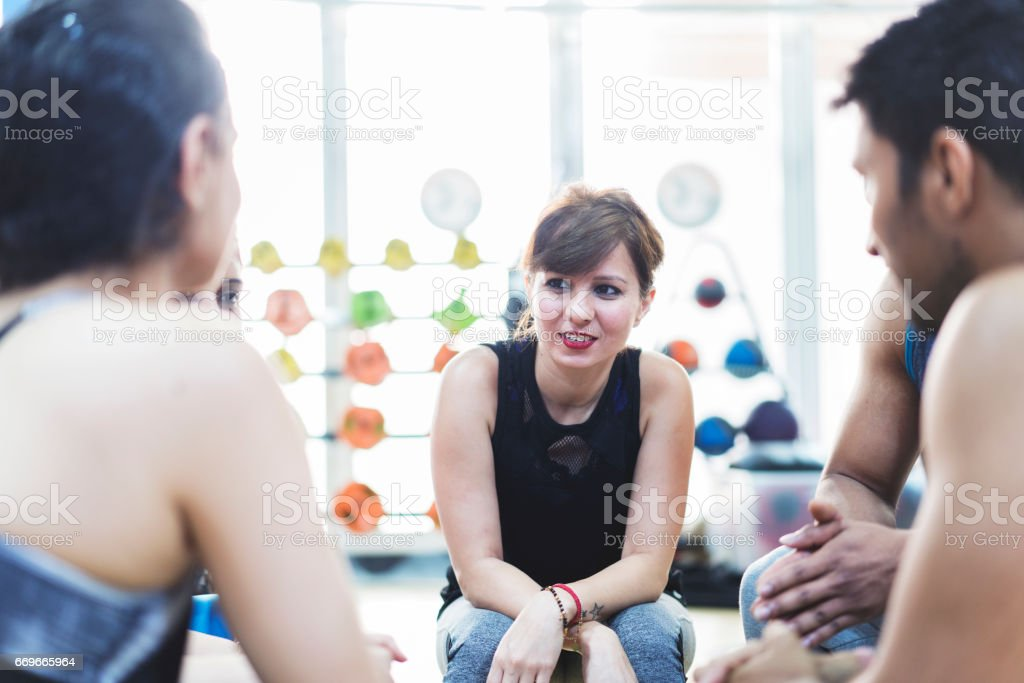 Girl listening carefully to fellow fitness class students stock photo