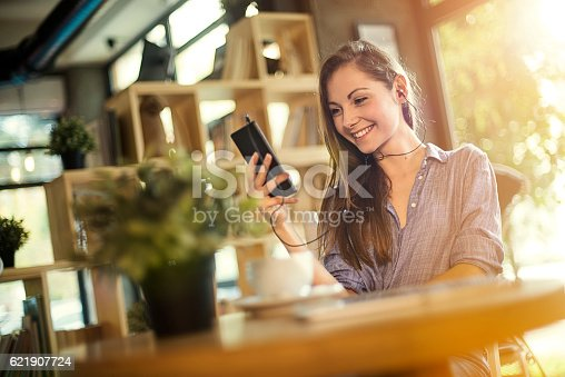 694187664 istock photo Girl listening music on mobile phone in a coffee shop 621907724