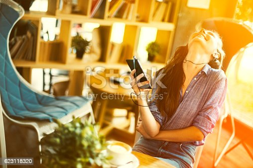 694187664 istock photo Girl listening music on mobile phone in a coffee shop 623118320
