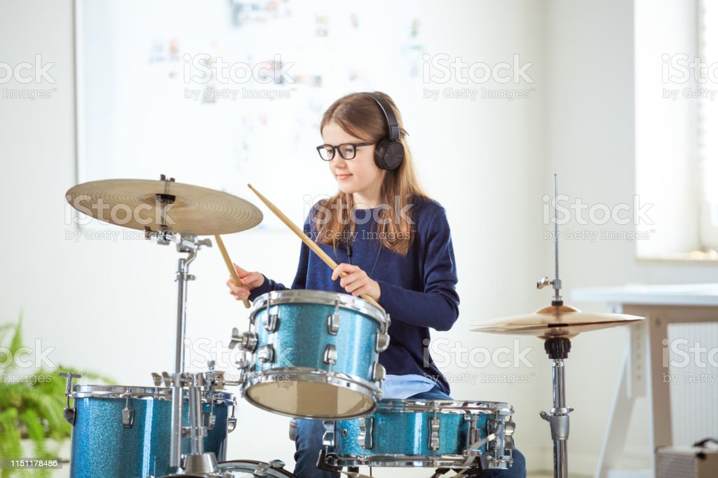 Girl listening music while playing drums Female drummer listening music through headphones while playing drums. Confident student is practicing in classroom. She is training at conservatory. 10-11 Years Stock Photo