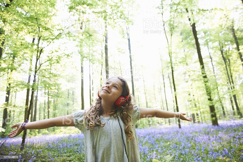 Girl listening to headphones in forest stock photo