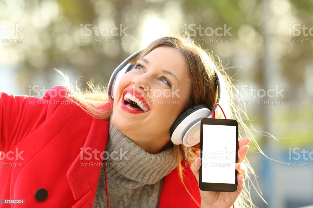 Girl listening to music and showing smartphone screen stock photo
