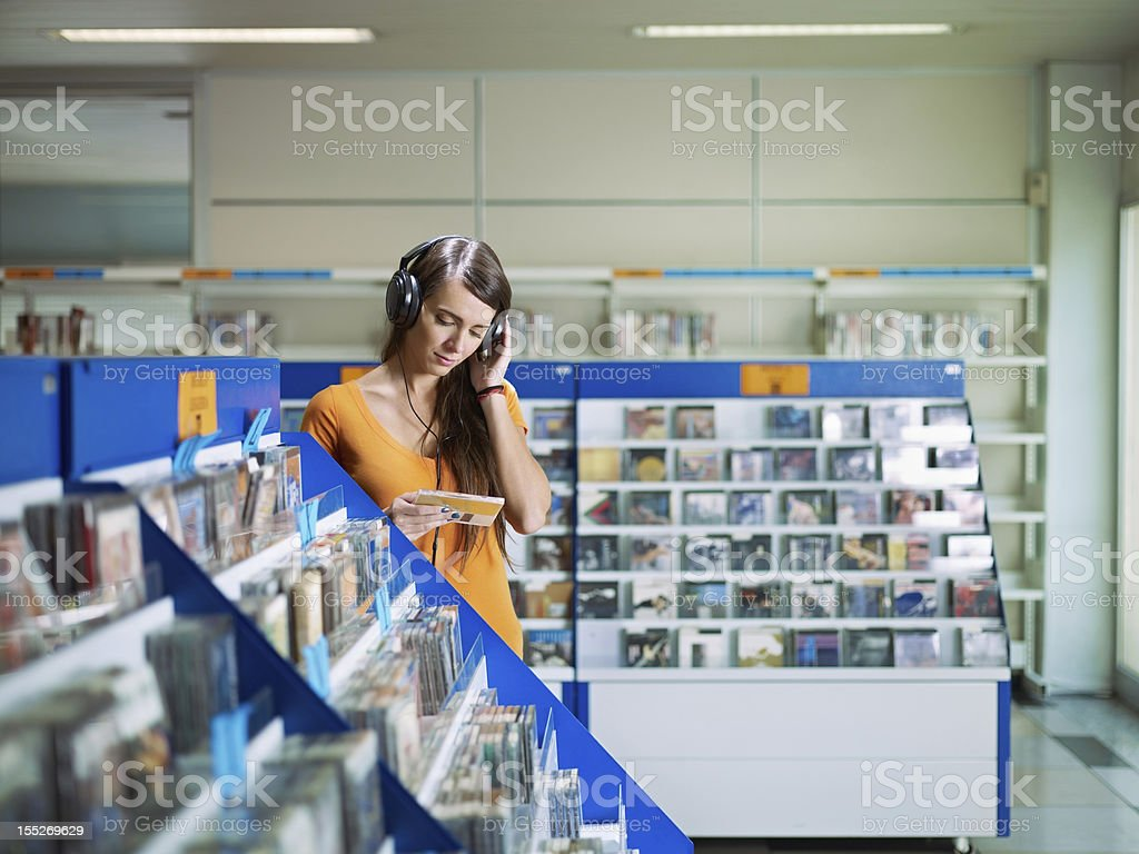 girl listening to music in cd store royalty-free stock photo