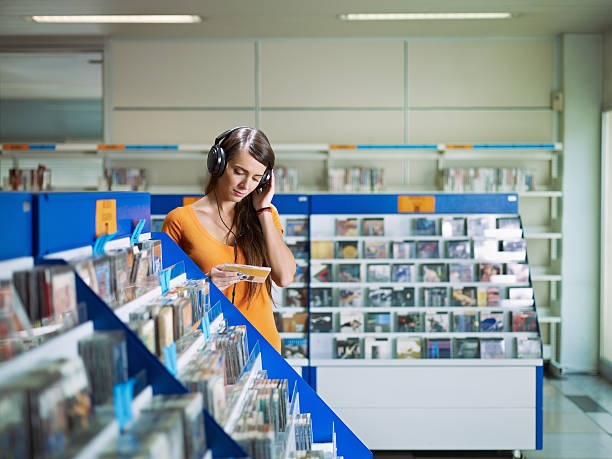 girl listening to music in cd store stock photo