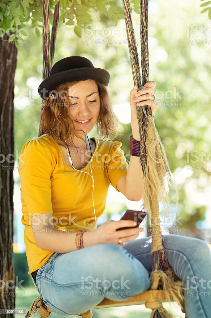 Girl listening to music on a swing stock photo