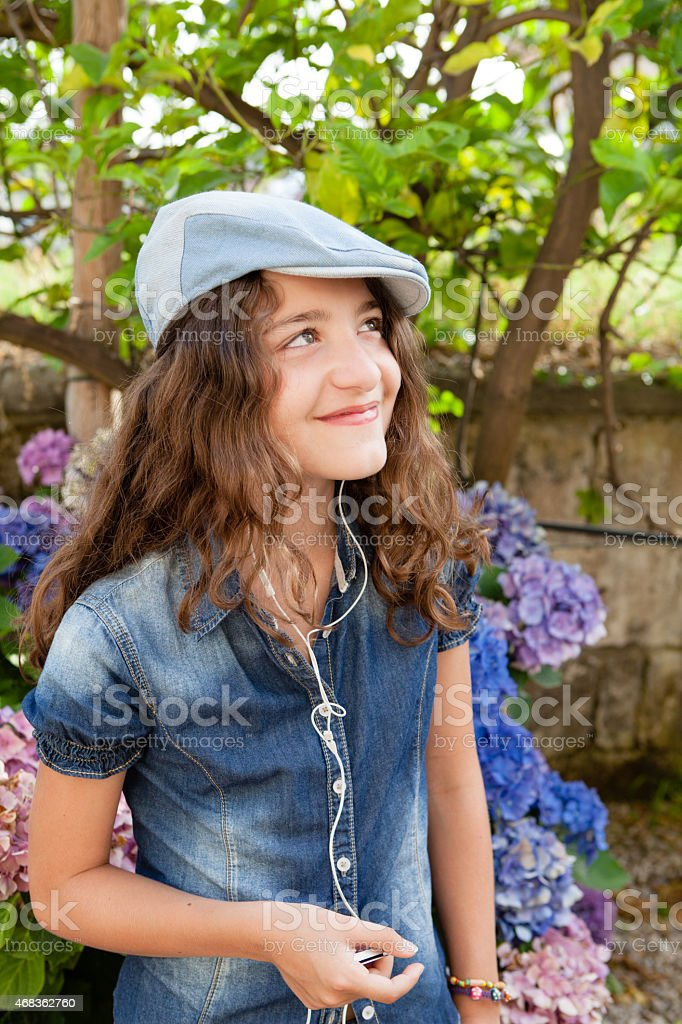 Girl listening to music on  Smartphone in the Garden royalty-free stock photo