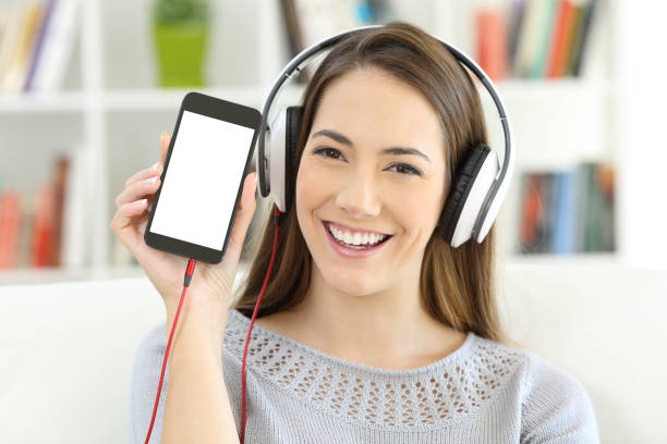 Girl listening to music showing   blank smart phone screen stock photo
