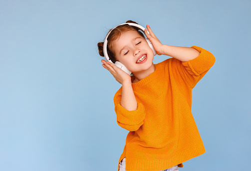 Adorable little girl in casual clothes pressing headphones to ears and smiling while listening to good music with closed eyes against blue background