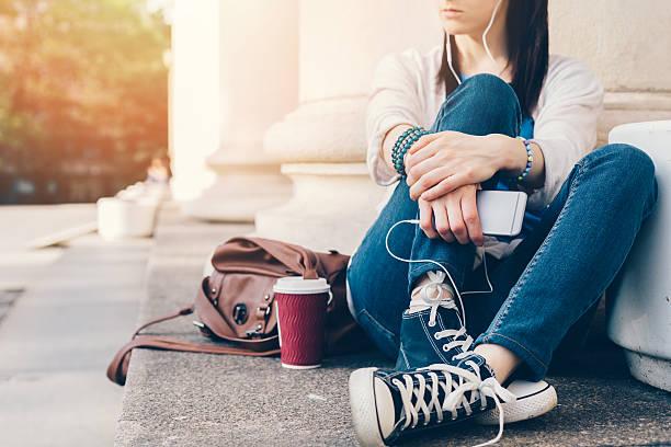 mädchen hören sie die musik auf smartphone - handtasche jeans stock-fotos und bilder