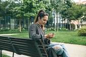 A young beautiful girl sits on a bench in a city park and plays music or a podcast or learns from audio lessons.