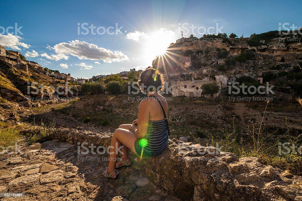 Girl look at the sun in Ginosa stock photo