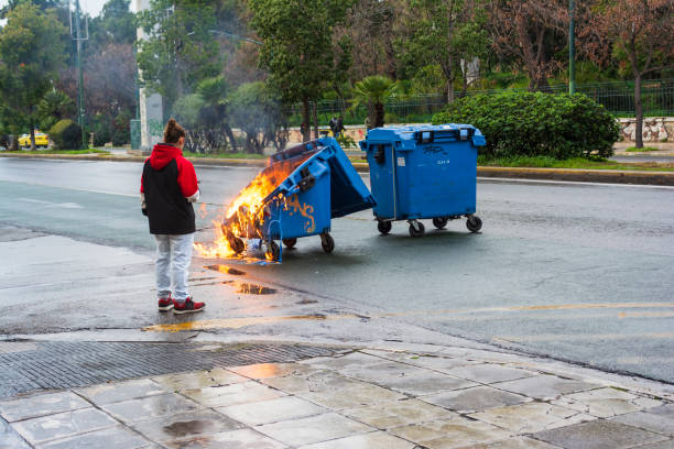 Girl looking a burnt and melted trash bin from fire in the city of Athens after a demonstration event Athens, Greece - January 20, 2019: Girl looking a burnt and melted trash bin from fire in the city of Athens after a demonstration event. dumpster fire stock pictures, royalty-free photos & images