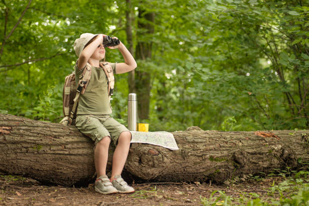 girl looking at birds through binoculars, camping in the woods - gids stockfoto's en -beelden