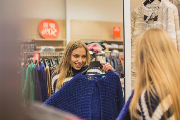 girl looking at cardigan in mirror - kleider günstig kaufen stock-fotos und bilder