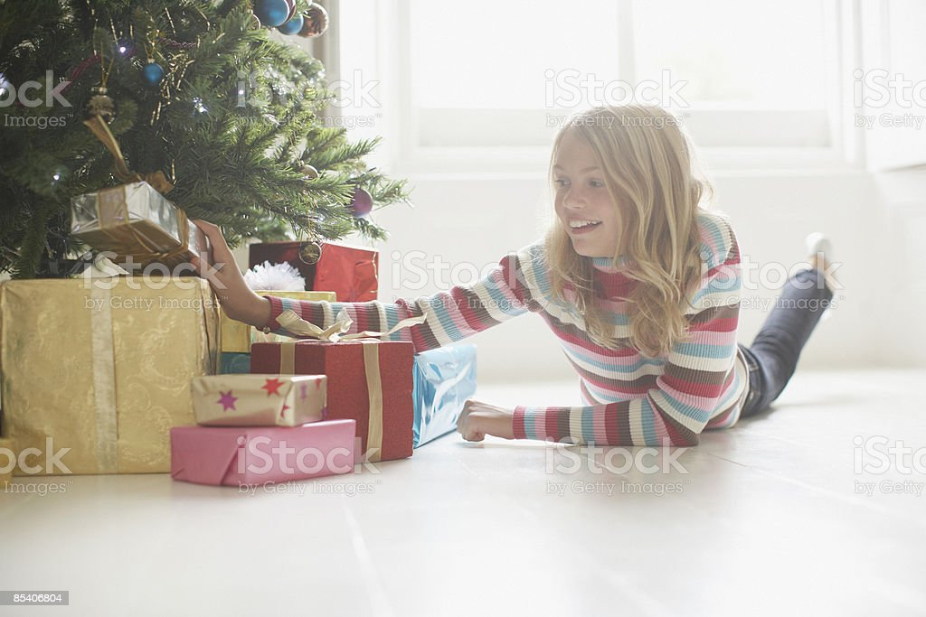 Girl looking at Christmas gifts under tree royalty-free stock photo