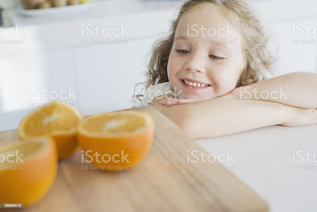Girl looking at cut oranges royalty-free stock photo