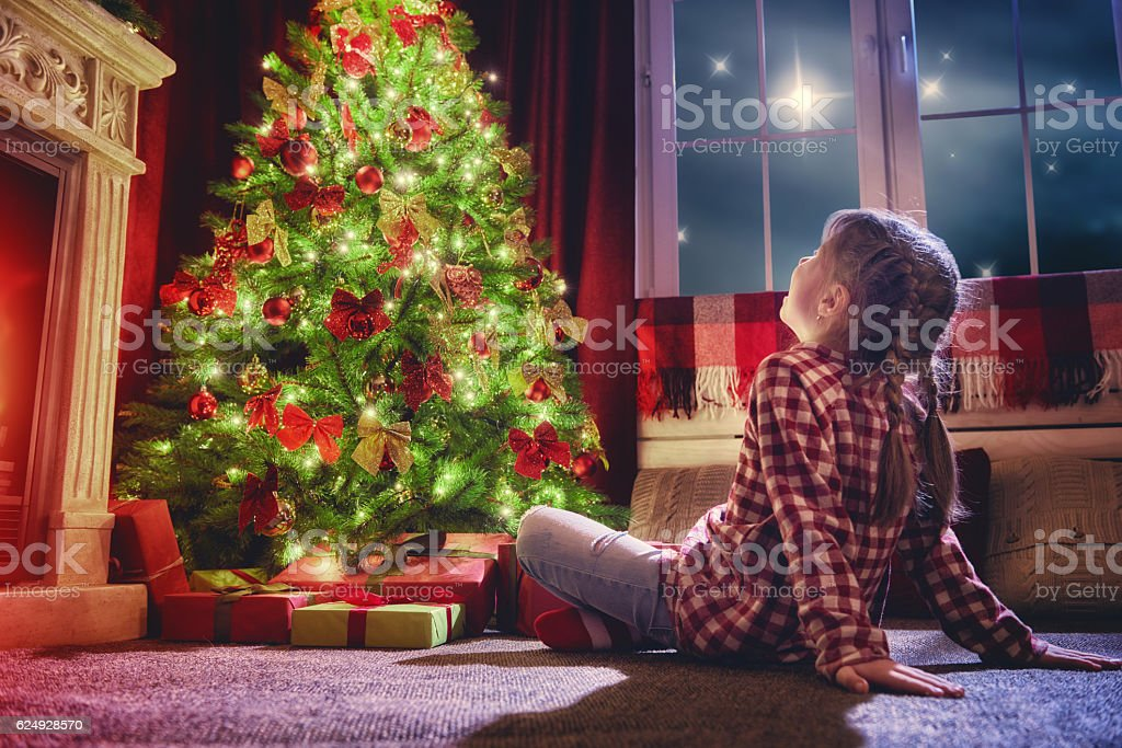Merry Christmas and Happy Holidays! Cute little child girl looking at...