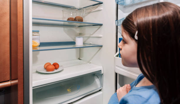 Girl looking at empty fridge due to a crisis Worried girl looking at the almost empty fridge due to a crisis poverty stock pictures, royalty-free photos & images