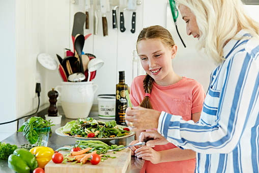 Girl looking at grandmother cooking in kitchen