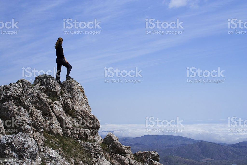 Girl looking at landscape from rock mountain top royalty-free stock photo