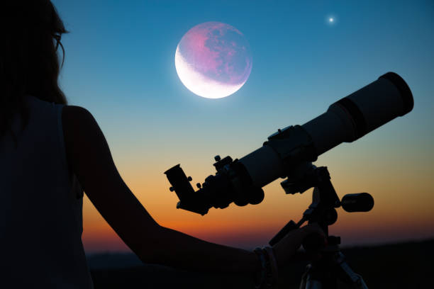 Girl looking at lunar eclipse through a telescope. My astronomy work. stock photo
