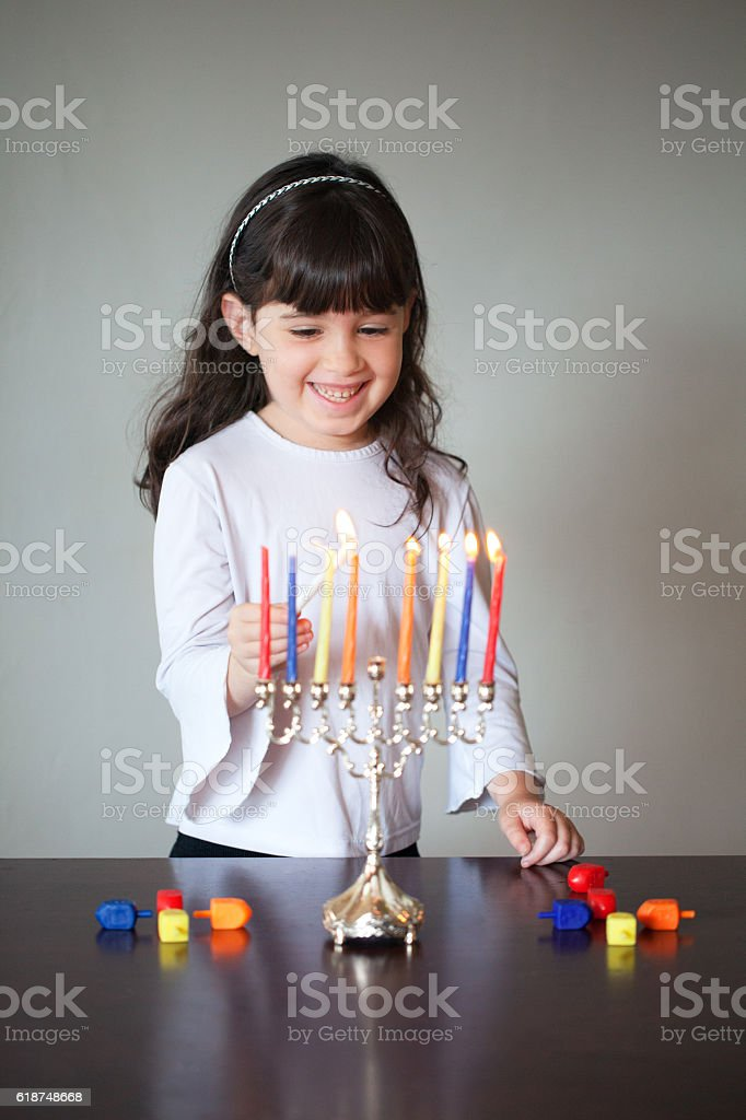 Girl looking at menorah for Hanukkah stock photo