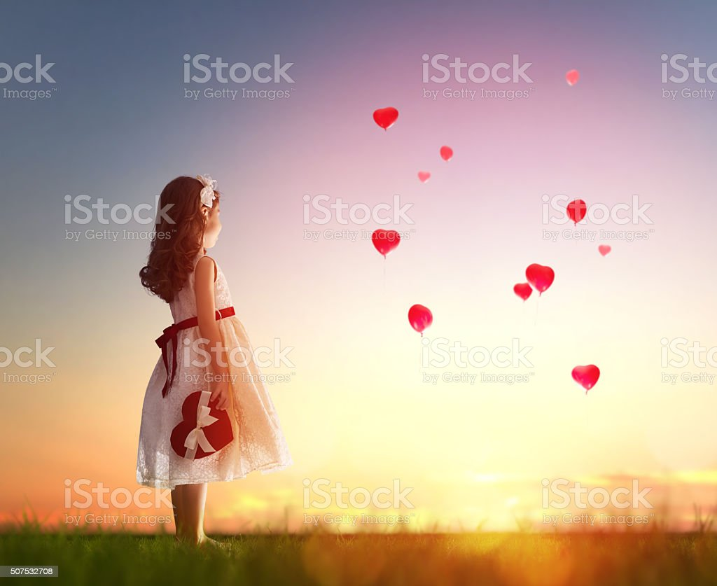 girl looking at red balloons stock photo
