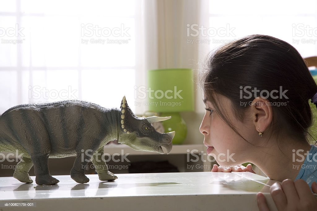 Girl (11-12) looking at statue of rhinoceros, side view royalty free stockfoto