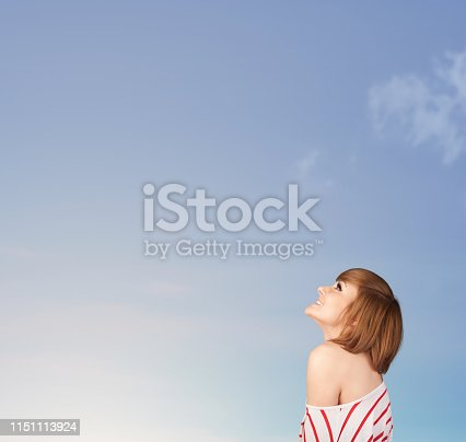 istock Girl looking at the blue sky copyspace 1151113924