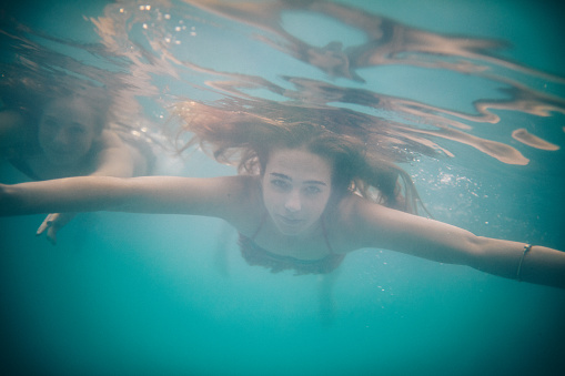 Teen girl floating underwater and looking at the camera while in a swimming pool