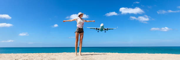 Girl looking at the flying plane above the sea stock photo