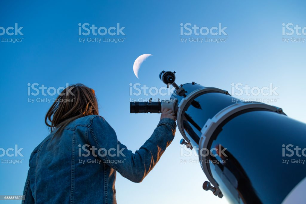 Girl looking at the Moon through a telescope. stock photo