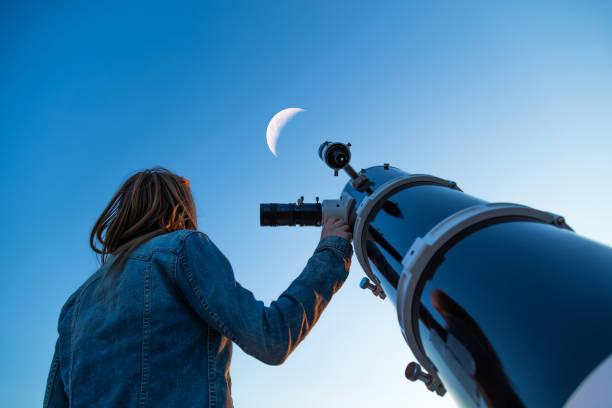 girl looking at the moon through a telescope. - astronomie photos et images de collection