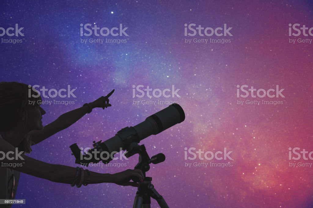 Girl looking at the stars with telescope beside her. Lizenzfreies stock-foto