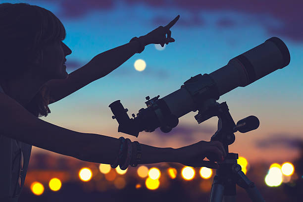 girl looking at the stars with telescope beside her. - astronomie photos et images de collection